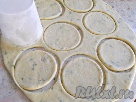 Далее тесто разделить на 4 части, каждую раскатать в пласт (стол присыпать мукой), толщиной около 0,5 см. Чашкой или стаканом вырезать кружочки.