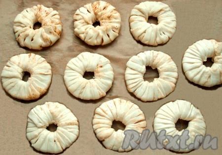 Полученными полосками слоеного теста обмотать кольца ананасов. На одно кольцо уйдёт приблизительно по две длинных полоски теста. Застелить противень пергаментом и выложить кольца на небольшом расстоянии друг от друга.