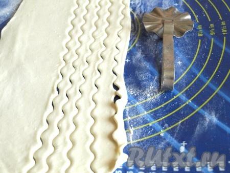 Слоёное тесто разморозить при комнатной температуре, раскатать толщиной 5 мм и нарезать на полоски шириной 7-10 мм. Нарезать можно ровно или фигурно.