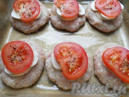 Далее на грибы положить по 0,5 чайной ложки сметаны или майонеза, затем - по кружочку помидора, чуть посолить и поперчить.