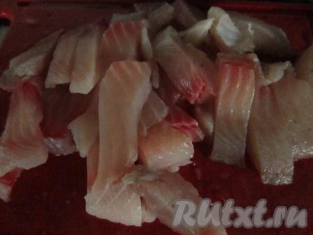 Пока овощи тушатся, порежьте рыбу кусочками, предварительно проверив, не остались ли в филе кости.