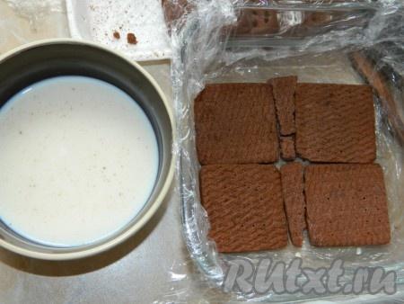 Форму для десерта застилаем пищевой пленкой. Печенье обмакиваем в молоко и выкладываем в форму в один слой.