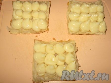 Нижние части выложить на разделочную доску или большое блюдо, с помощью кондитерского мешка или полиэтиленового пакета высадить небольшие шарики крема по всей поверхности коржа.{amp}#xA;
