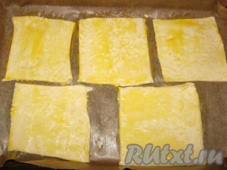 Заранее разогреть духовку до 220 градусов. Размороженное тесто разрезать на одинаковые части - квадраты или прямоугольники, выложить их на противень, застеленный пергаментом, смазать желтком.{amp}#xA;