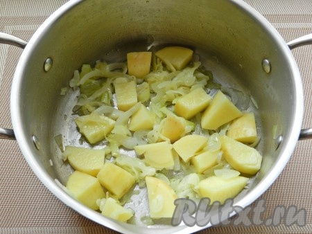 Картофель нарезать кубиками и добавить в кастрюлю. Влить 700 мл воды, посолить, поперчить и варить 5 минут.