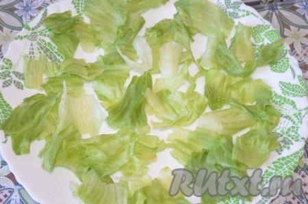 Курицу разобрать на волокна или порезать. Порвать листья салата, выложить на блюдо.