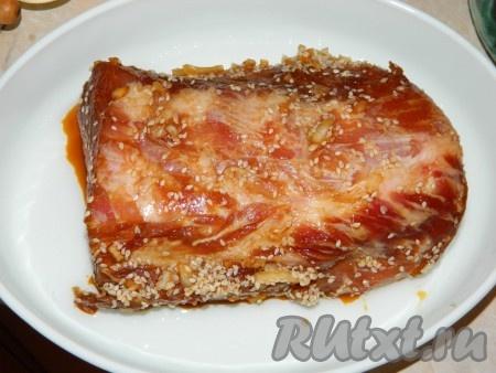 Достать мясо из маринада, выложить в смазанную маслом форму и поставить печься, не накрывая, в разогретую духовку на 50-60 минут при температуре 200 градусов.