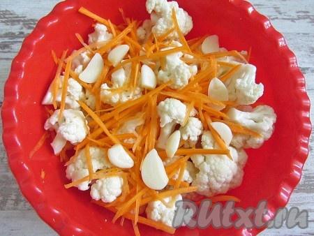 Соедините капусту, морковь и дольки чеснока. Добавьте специи.