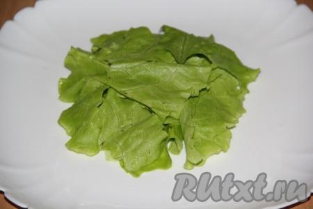 Листья салата вымыть, обсушить и порвать на небольшие кусочки. Выложить листья салата на плоскую тарелку.
