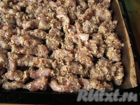 Противень застелите бумагой для выпечки и достаточно обильно смажьте растительным маслом. Выкладывайте куриные кусочки на противень в один слой.