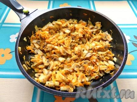 В сковороде разогреть масло, выложить шампиньоны и обжарить до испарения жидкости. Затем добавить лук, морковь и обжарить все вместе до легкого золотистого цвета.