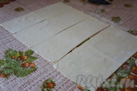 Стол присыпать мукой, тонко раскатать слоёное тесто. Разрезать на прямоугольники.