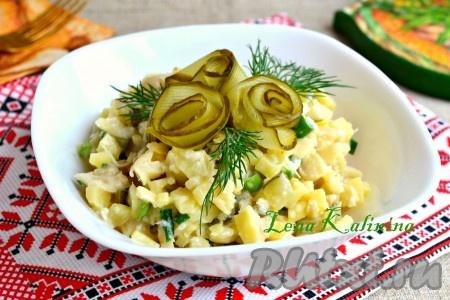 Выложить простой, но очень вкусный рыбный салат с картофелем в салатник, украсить маринованными огурчиками и зеленью.