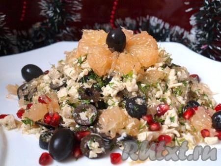 Выкладываем салат на тарелку, украшаем маслинами, зёрнами граната, кусочками грейпфрута и подаём к столу.