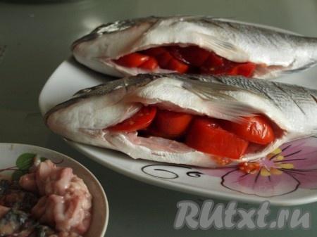 Рыбку почистить, удалить внутренности и жабры. Хорошо промыть и обсушить. С одной стороны сделать на дорадо косые надрезы. Нарезать кружочками помидоры и поместить внутрь каждой рыбёшки. Рыбку положить в контейнер и мариновать 1 час.