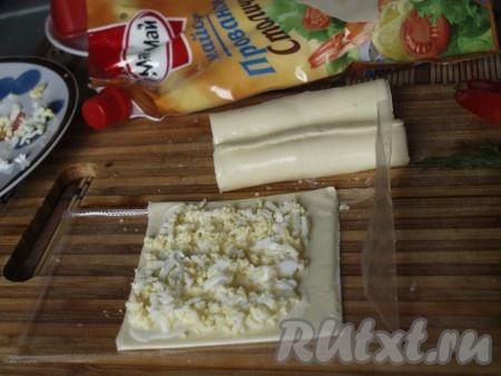 Пластинки сыра слегка смазываем майонезом, посыпаем яйцами и сворачиваем в трубочки - это будут свечи.