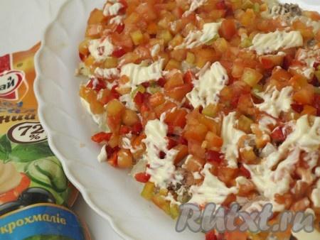 Из болгарского перца сразу вырезаем язычки огня, оставшийся перец и помидоры нарезаем мелкими кубиками. Смешиваем порезанные помидоры и перец, выкладываем следующим слоем, солим, смазываем майонезом.