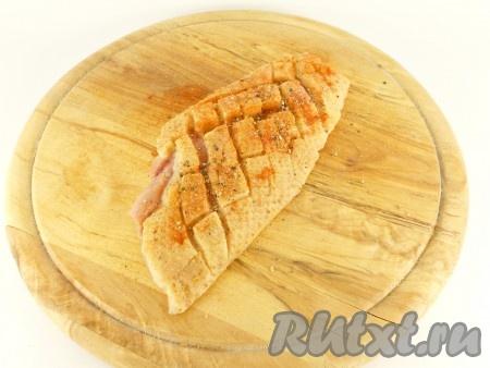 Посолить, посыпать паприкой и свежемолотым перцем, втирая специи в разрезы.