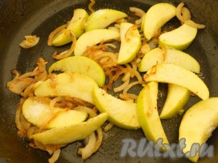 Огонь уменьшить и в ту же сковороду с жиром поместить чеснок, обжарить его до румяности и выбросить. Далее выложить в сковороду лук, обжарить 2 минуты, добавить яблоки, посыпать сахаром. Перемешать и тушить яблоки, пока сахар не начнет превращаться в карамель.
