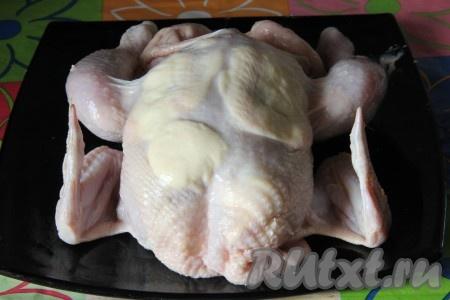Сливочное масло смешать с чесночным порошком и аккуратно распределить под кожей курицы со всех сторон.
