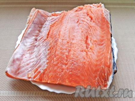 Рыбу очистить, удалить плавники, вырезать хребет и оставить филе на коже.