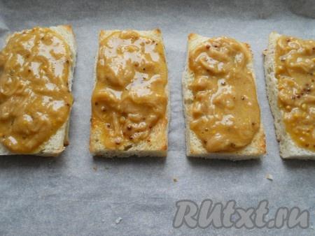 Смазать ломти хлеба сырной массой сверху, поместить их на противень и отправить в разогретую до 180-190 градусов духовку на 7-10 минут.