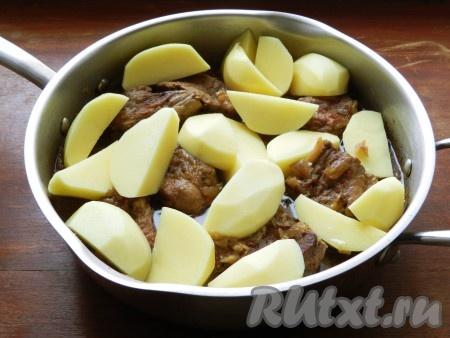 Добавить к говядине очищенный и нарезанный крупными ломтиками картофель, накрыть крышкой и готовить жаркое еще 30 минут, до мягкости картошки.