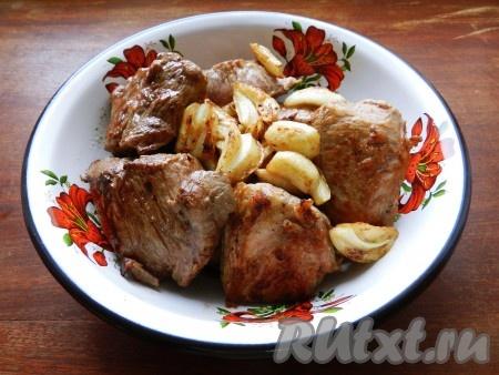 Обжаренное мясо переложить на тарелку, в сотейник выложить чеснок и обжарить на среднем огне 2 минуты. Обжаренный чеснок шумовкой переложить к мясу.