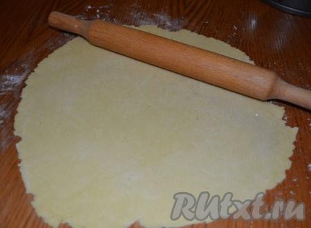 Выбираем самый большой кусочек теста и раскатываем его в тоненький пласт. Выкладываем в форму для выпечки, формируя достаточно высокие бортики.