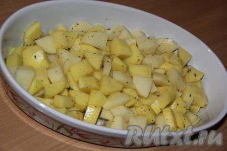 Картофель почистить, нарезать средними кубиками, посолить, добавить специи я использовала специи для картофеля). Выложить картошку на дно жаропрочной формы.