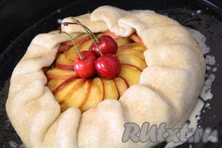 Аккуратно завернуть начинку в тесто. Сделать небольшие нахлёсты теста, слегка их прижимая. Края теста смазать взбитым желтком, присыпать коричневым сахаром. В середину начинки из персиков и яблок положить пару ягодок черешни. Поставить пирог в разогретую духовку и выпекать при 180-200 градусах примерно 30-35 минут, до золотистой корочки.