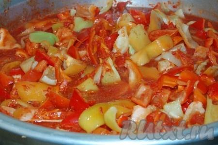 Отправим натертую морковь в томатное пюре и варим в кастрюле 20 минут, после чего отправим туда же и очищенный от семян, нарезанный перец.