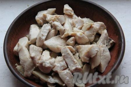 Куриную грудку отделяем от костей, режем на небольшие кусочки, обжариваем на оливковом масле со всех сторон на сильном огне до золотистого цвета и выкладываем на грибы.