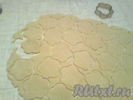 Рабочий стол подпылить мукой, выложить на него тесто. Раскатать тесто толщиной 3-5 мм, больше муки не подсыпать, можно скалку слегка посыпать мукой, чтобы тесто не прилипало при раскатывании. От толщины теста зависит мягкость печенья. Из теста толщиной 0,5 см получится более мягкое печенье, а из теста толщиной 0,3 см - более хрупкое. Вырезать из раскатанного теста фигурки выемкой или порезать ножом тесто на квадраты, прямоугольники или любые другие фигурки.