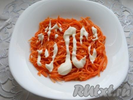 Первым слоем на тарелку выложить корейскую морковь (не сильно измельчить ножом), смазать немного майонезом.