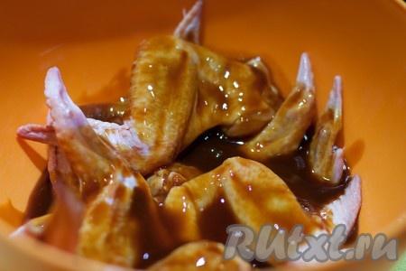 Замаринуйте куриные крылья минут на 10-15 в смеси кетчупа и соевого соуса.