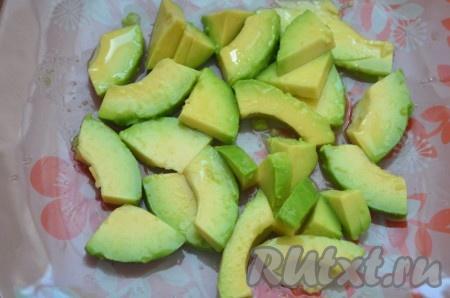 Авокадо разрезать вдоль пополам, достать косточку. Сделать надрезы, чайной ложкой выбрать мякоть, которую затем нарезать на небольшие дольки. Можно полить лимонным или апельсиновым соком.