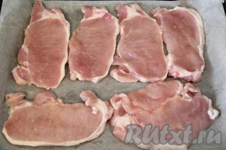 Свинину порезать на порционные кусочки, не тонко. Слегка отбить кусочки свинины. Посолить и поперчить по вкусу. Противень для запекания выстелить пергаментом. Выложить кусочки свинины на пергамент.