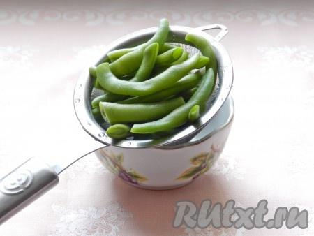 Зеленую фасоль если замороженная, не размораживать) опустить в кипящую подсоленную воду и отварить в течение 5 минут. Затем откинуть на сито и промыть холодной водой.
