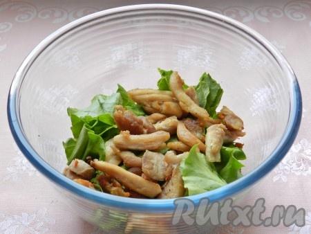 В салатницу выложить порванные руками листья салата и куриное мясо.