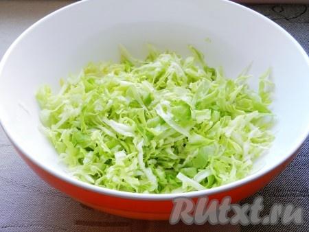 Нашинковать капусту. Молодую капусту заранее солить и мять руками не нужно, она и так достаточно сочная. Если вы используете для салата капусту прошлогоднего урожая, то посолите по вкусу и слегка помните.