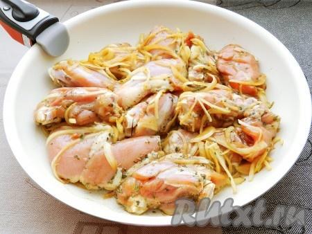 Выложить куриные бедра вместе с луком в сковороду без масла и обжарить на сильном огне.