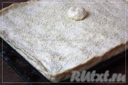 Смазать пирог молоком, посыпать кунжутом. Выпекать в разогретой духовке примерно 40-55 минут при температуре 180 градусов.