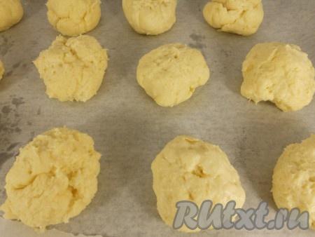 Разделить тесто на 15-17 кусочков. Чуть смачивая руки в воде, скатать шарики (слишком гладкие и ровные делать не старайтесь, просто скатайте комочки). Выложить комочки теста на противень, застеленный пергаментом, на расстоянии 4-5 см друг от друга.
