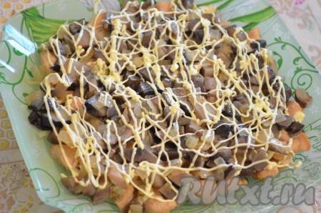 Затем кладём слой грибов с луком, можно посолить, рисуем сеточку из майонеза.