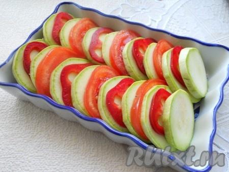 Сладкий болгарский перец очистить от семян. Помидоры и перец нарезать, как и кабачок, кружочками. В форму для запекания выложить нарезанные овощи вертикально, чередуя их друг с другом.