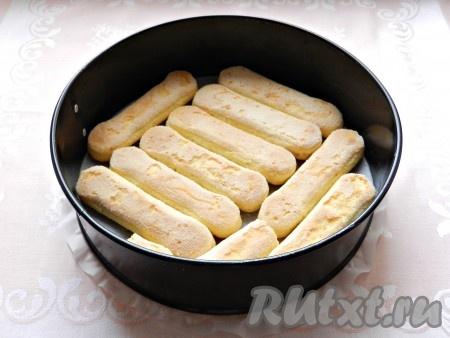 Форму для выпечки застелить бумагой. На дно выложить печенье савоярди.