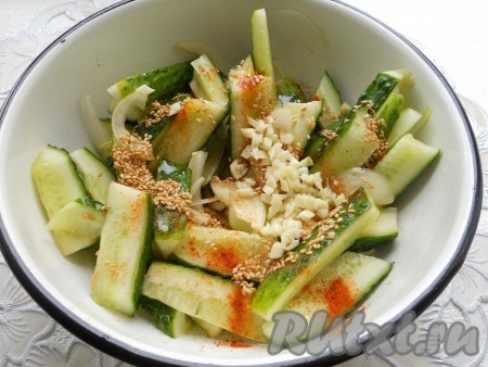 Добавить обжаренный кунжут вместе с маслом в китайский салат из огурцов. Также добавить измельченный чеснок. По вкусу досолить (если понадобится). Хорошенько все перемешать.