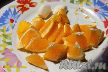 Отдельно в тарелочке нарезать вымытый, неочищенный от кожуры апельсин и раздавить ножом чеснок.