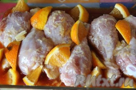 В форму выкладываем куриные ножки, затем раскладываем чеснок и апельсин. Заливаем все приготовленным апельсиновым соусом.